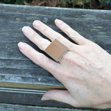 Photo of wooden flooring sample silver-plated ring on hand