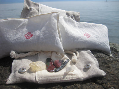 root chakra bag Chakra Balance Bags are composed of an outer hemp bag with an embroidered chakra coloured symbol. Inside are two smaller herbal pouches with blends of organic herbs and organic essential oils. These two pouches are stamped with chakra distinct coloured symbols for identity. Located within the hemp bag is a small drawstring bag containing 5 crystals. Three are chakra specific healing crystals, an extra crystal to continuously cleanse and clear the energies of the bag and a final crystal to am