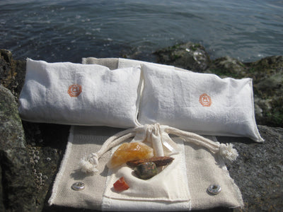 sacral chakra bag Chakra Balance Bags are composed of an outer hemp bag with an embroidered chakra coloured symbol. Inside are two smaller herbal pouches with blends of organic herbs and organic essential oils. These two pouches are stamped with chakra distinct coloured symbols for identity. Located within the hemp bag is a small drawstring bag containing 5 crystals. Three are chakra specific healing crystals, an extra crystal to continuously cleanse and clear the energies of the bag and a final crystal to