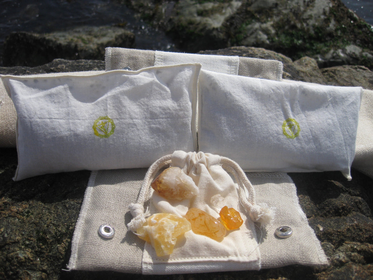 solar plexus Chakra Balance Bags are composed of an outer hemp bag with an embroidered chakra coloured symbol. Inside are two smaller herbal pouches with blends of organic herbs and organic essential oils. These two pouches are stamped with chakra distinct coloured symbols for identity. Located within the hemp bag is a small drawstring bag containing 5 crystals. Three are chakra specific healing crystals, an extra crystal to continuously cleanse and clear the energies of the bag and a final crystal to ampli
