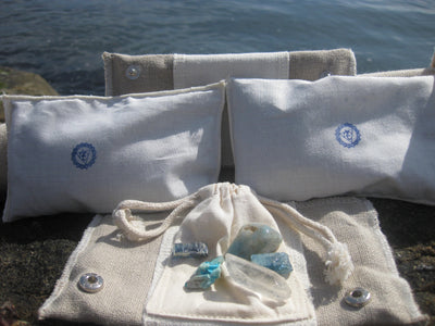 throat Chakra Balance Bags are composed of an outer hemp bag with an embroidered chakra coloured symbol. Inside are two smaller herbal pouches with blends of organic herbs and organic essential oils. These two pouches are stamped with chakra distinct coloured symbols for identity. Located within the hemp bag is a small drawstring bag containing 5 crystals. Three are chakra specific healing crystals, an extra crystal to continuously cleanse and clear the energies of the bag and a final crystal to amplify and