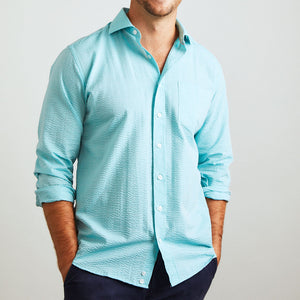 A solid look for a solid guy. The light teal hues of the ocean are calling you in this shirt. Seersucker, lightweight, and supremely cool. Available in short or long sleeve.  100% Cotton Seersucker • Spread Collar • Long Sleeve • Chest Pocket • Machine Washable • Made in Italy