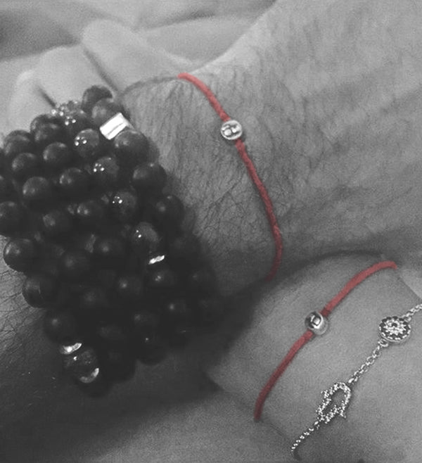 black and white photo of wrists wearing modern om red string bracelets
