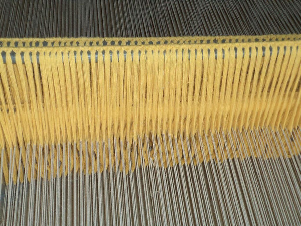 The vertical loom on which hand-knotted rugs are made