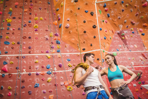 Two climbers on date at the climbing gym talking it up between climbs