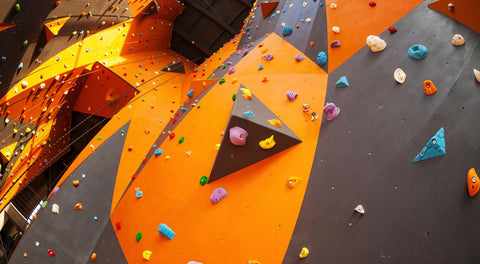Looking up at tall walls in a climbing gym covered with many routes