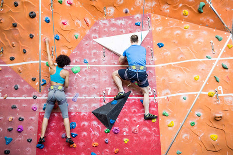Two climbers on a date sport climbing next to each other on adjacent routes in the gym