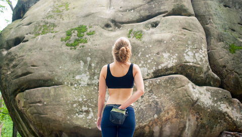 Woman climber looking at a boulder outdoors to figure out her beta