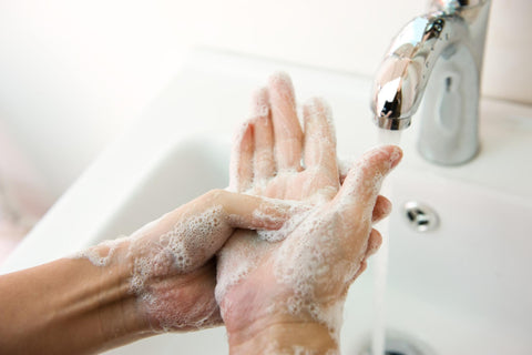 Climber washing hands using soap and cold water after a session