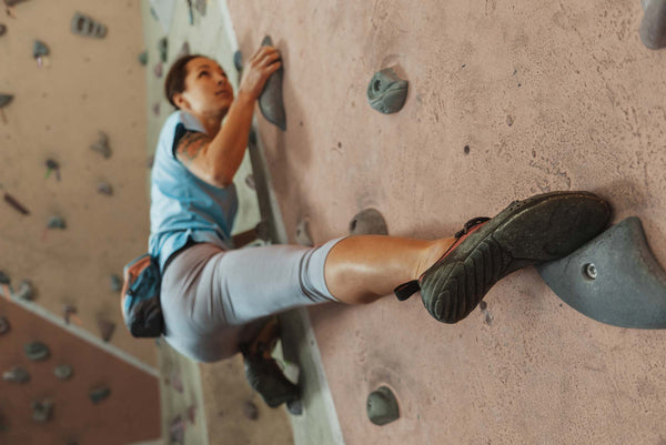 Female climber on the gym wall with hips out to the left