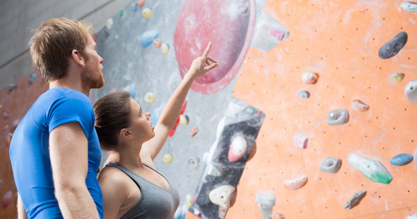 Two climbers talking through a route to make sure both understand how to spot a fall