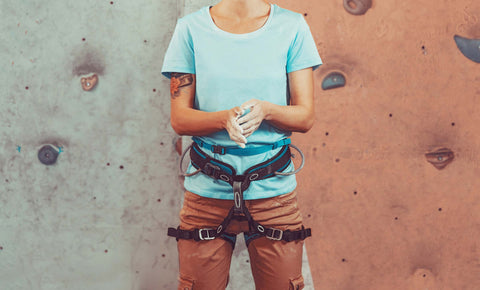 Women in harness clapping her chalked hands together ready to start climbing