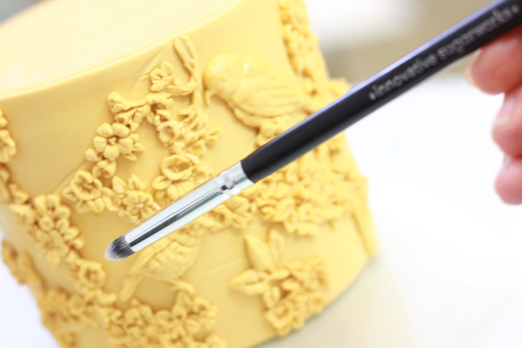 Using Innovative Sugarworks Artists' Brushes to apply molded fondant to cake