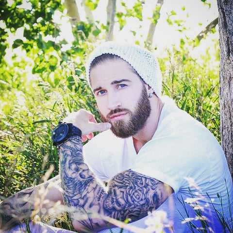 Lumbersexual (hipster, metrosexual with a beard) wearing a beanie with a Treehut wood watch and floral tattoos