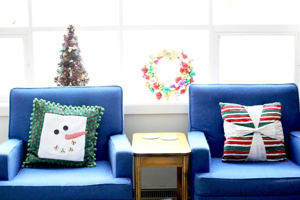 christmas decorations snow man pillow and striped green and red pillow blue vintage 50's chairs
