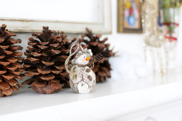 snow man decoration on fireplace mantle, pine cones christmas decorations