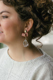 girl with curly hair in sparkle silver sweater with pink drop large earrings
