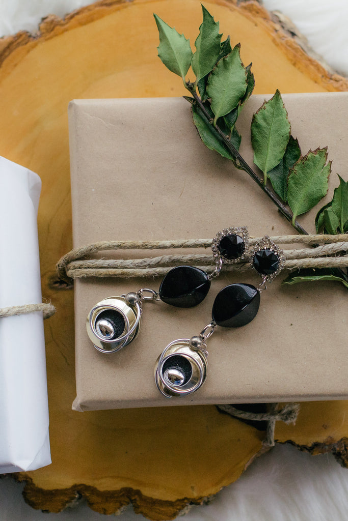 black and silver vintage earrings on top of kraft brown gift wrapped paper with holly on wood