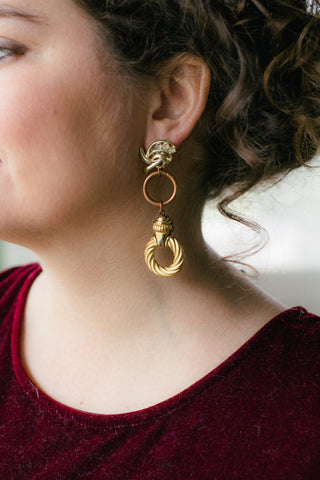 girl with curly hair wearing long gold hoop statement earrings handmade in toronto
