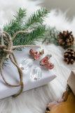 pink Japanese inspired earrings laying on white gift with twine bow and greenery