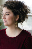 curly hair pinned up with girl wearing cranberry velvet shirt with long gold purple and pearl statement earrings