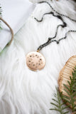 vintage gold locket surrounded by greenery on white fur background flat lay handmade in toronto