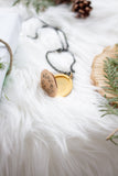vintage locket surrounded by greenery on white fur background flat lay handmade in toronto