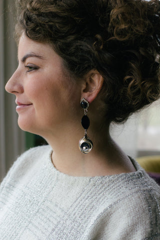girl with curly brown hair with long black and silver vintage earrings with silver sparkly sweater
