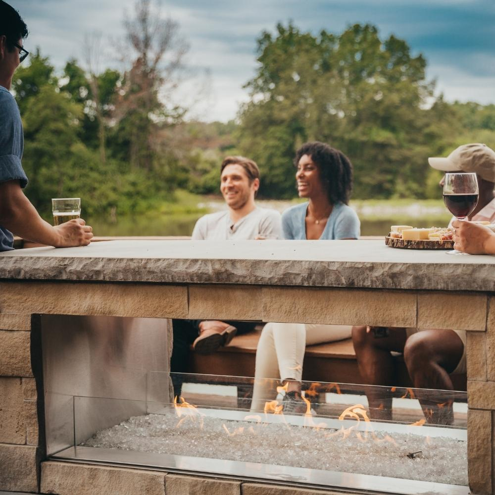 People Enjoying Drinks and Snacks by the See-Through Fireplace