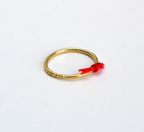 A delicate ring with engraving detail and a small red thread tied to the... click for more information