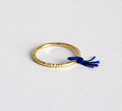 A delicate gold ring with engraving detail and a small cobalt thread tie... click for more information