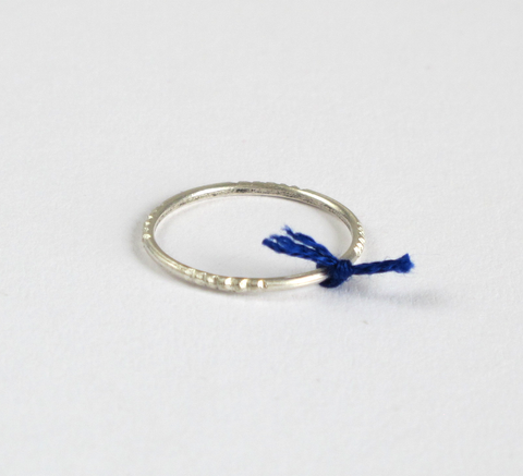 A delicate silver ring with engraving detail and a small cobalt thread t... click for more information
