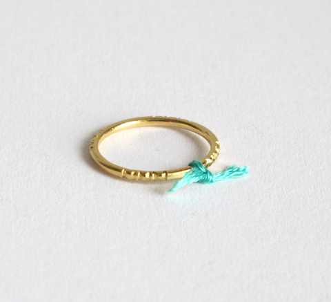 A delicate gold ring with engraving detail and a small aqua thread tied ... click for more information