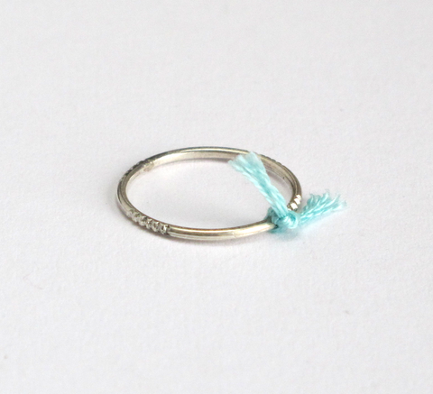 A delicate silver ring with engraving detail and a small mint thread tie... click for more information