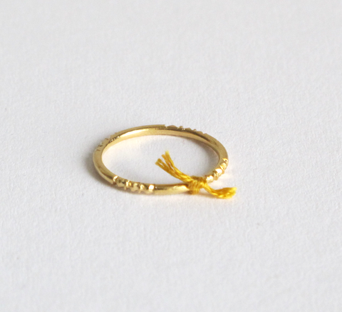 A delicate silver ring with engraving detail and a small mustard thread ... click for more information