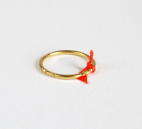 A delicate gold ring with engraving detail and a small orange thread tie... click for more information