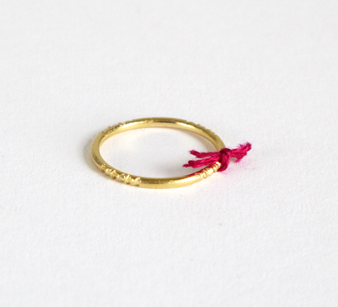 A delicate gold ring with engraving detail and a small purple thread tie... click for more information