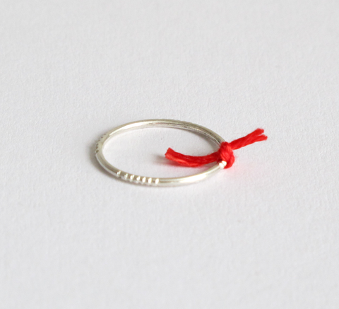 A delicate silver ring with engraving detail and a small red thread tied... click for more information