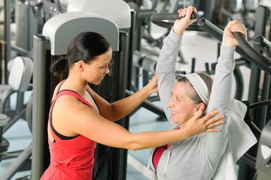 Older woman training in a gym with a trainer