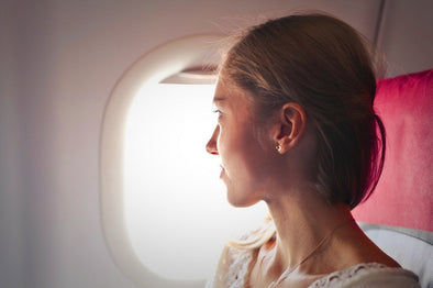 Female passenger looking out a plane window