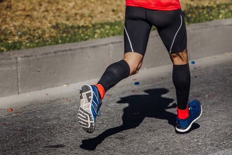 Man running wearing calf compression sleeves