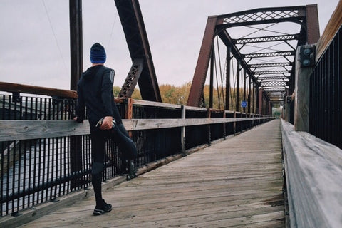 Runner wearing TXG compression socks stretching on a bridge