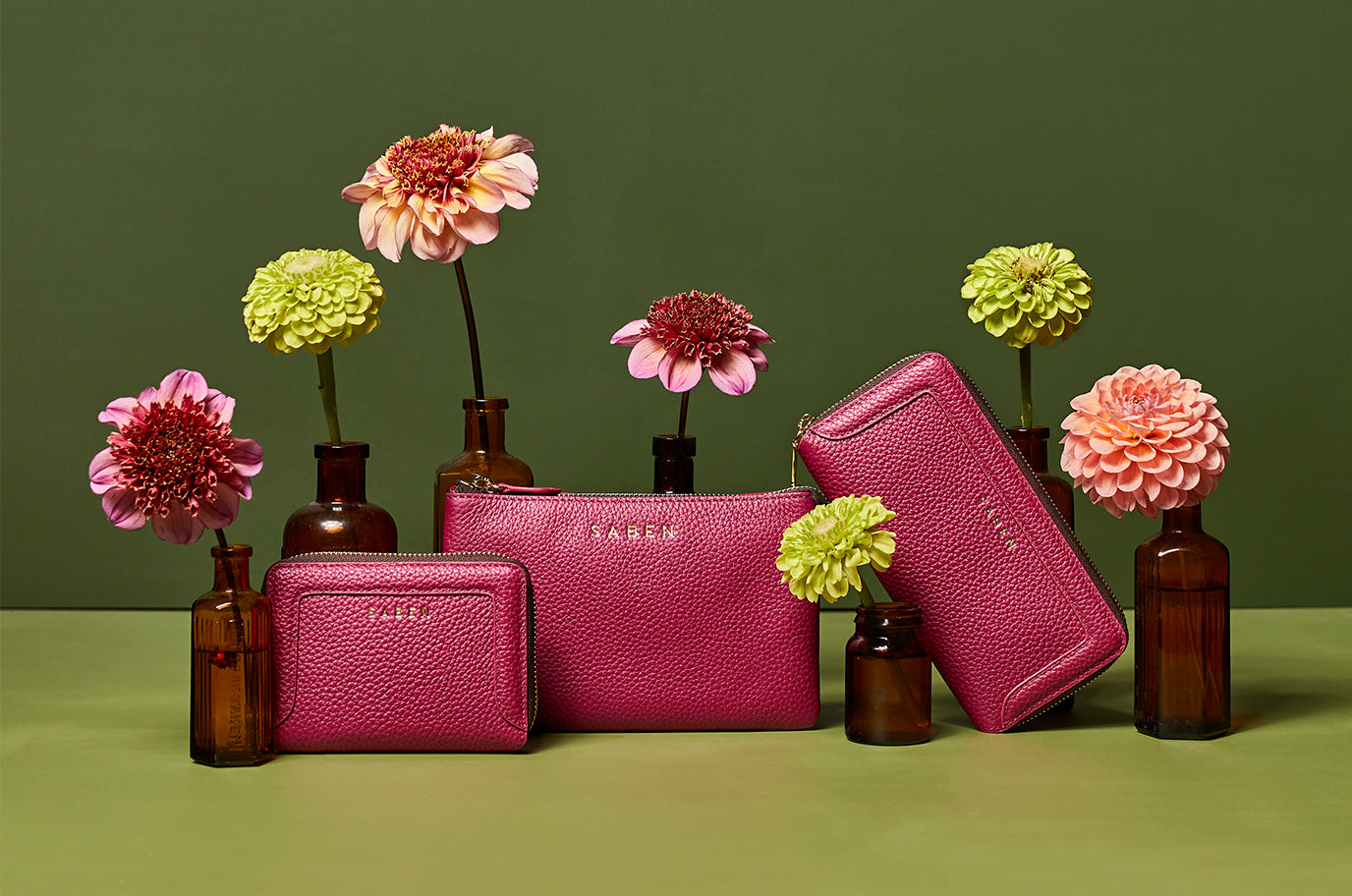 new saben orchid pink leather wallets and handbags sit on green background