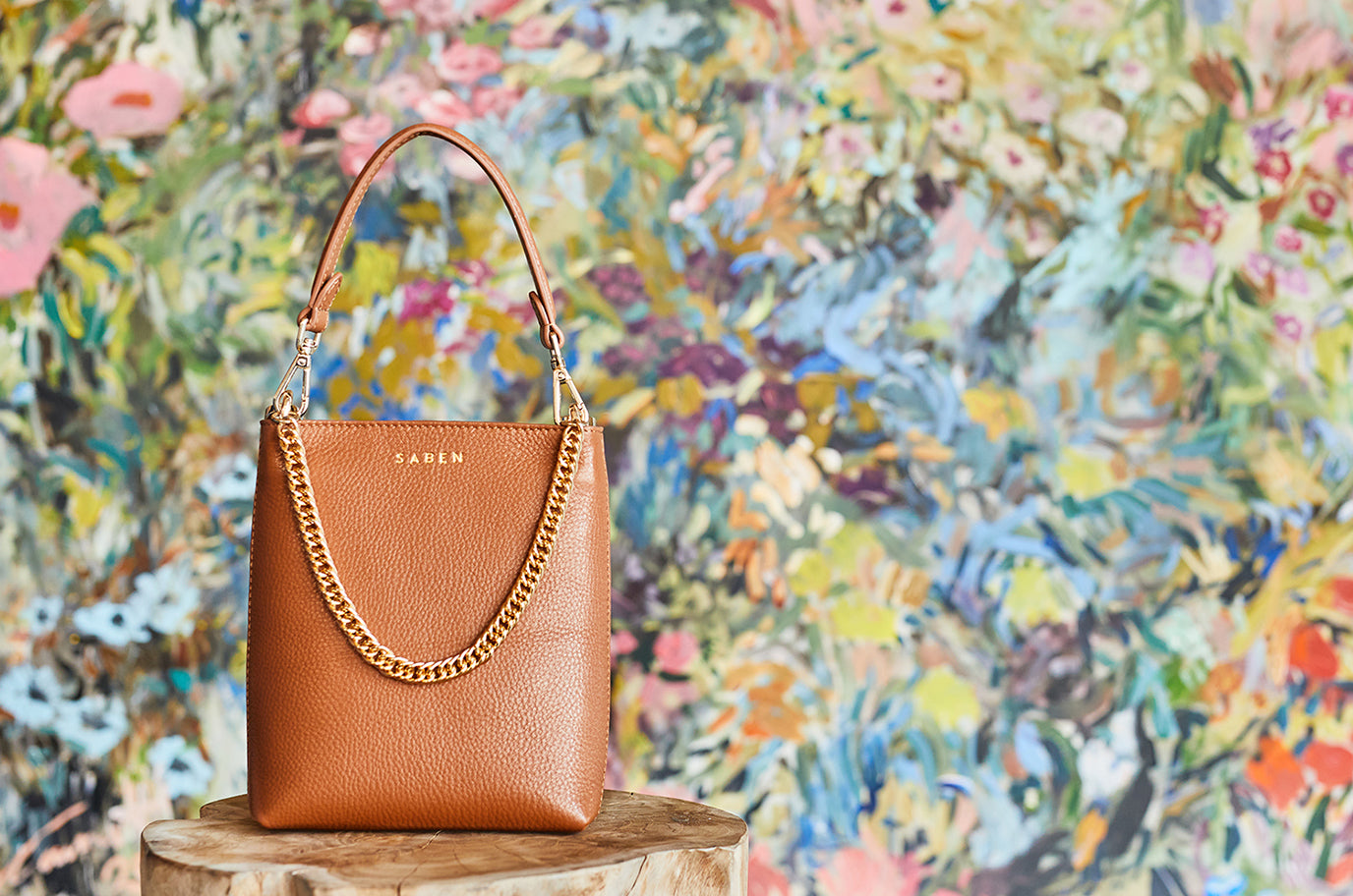 new saben handbag coco in clay colour sitting in front of painting by carmel van der hoeven of turua gallery
