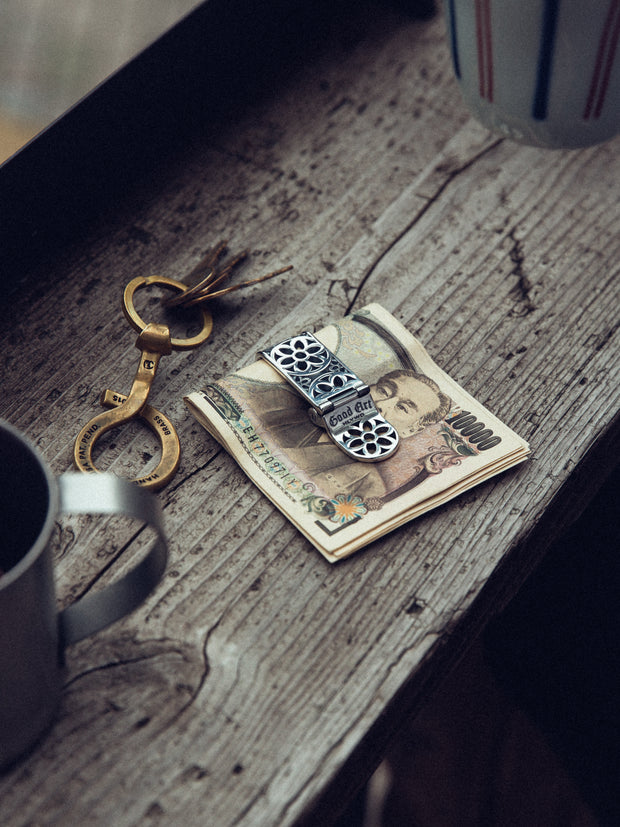 Money clip shown with money inside, next to the Belt Loop buddy and some coffee.