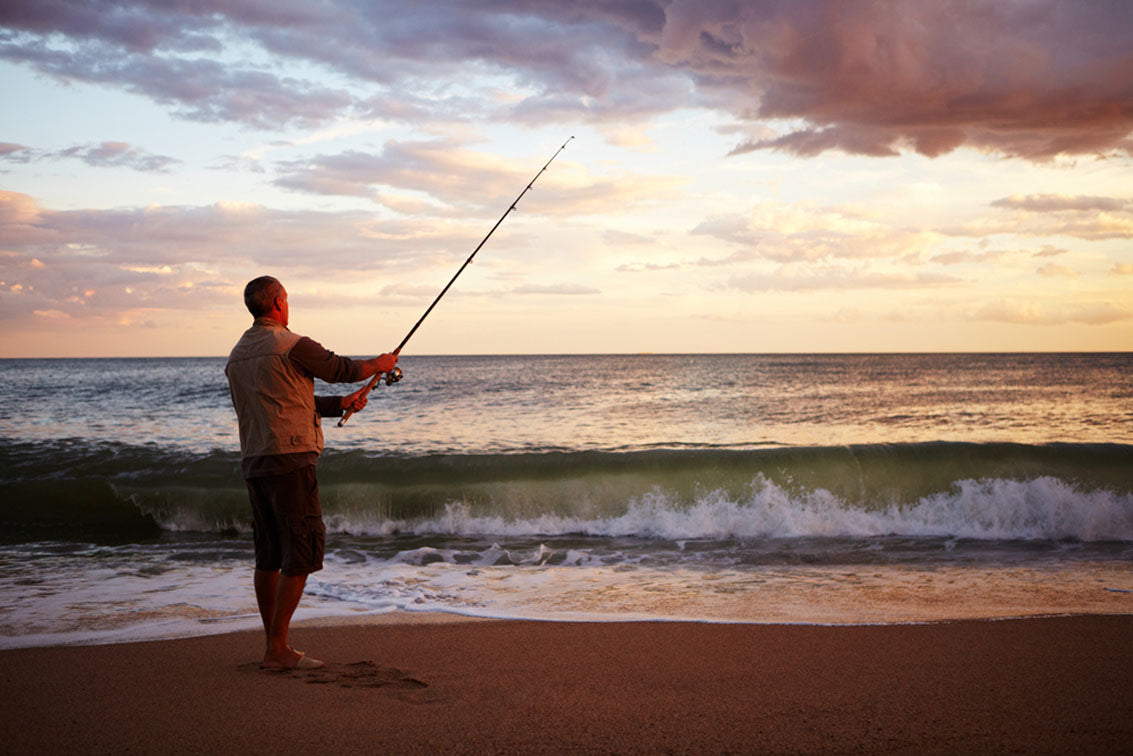 Man casting a fishing line into early morning surf
