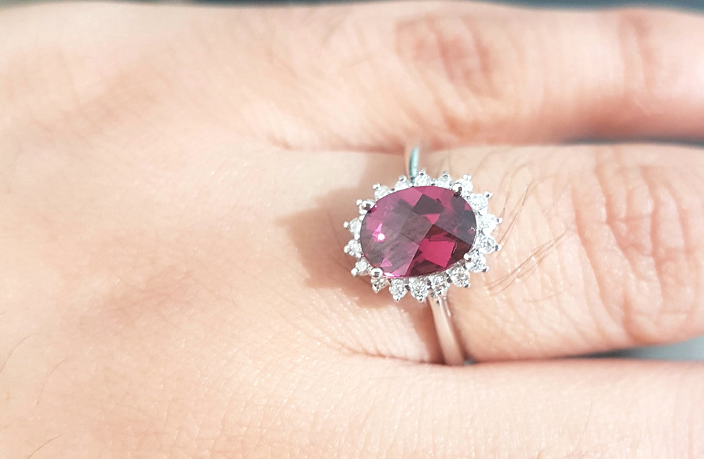 1.25ct Oval Cut Garnet | 0.20cts Round Brilliant Cut Diamonds | Halo Design Ring | 14kt White Gold