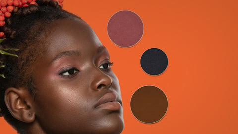 Black model with deep skin tone wearing all natural makeup by conscious beauty brand SAPPHO with three powder refills on a warm orange background