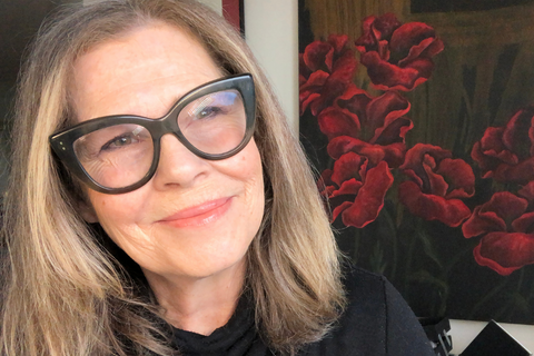 JoAnn Fowler, celebrity makeup artist and natural makeup brand founder, gazing while in front of red flower painting