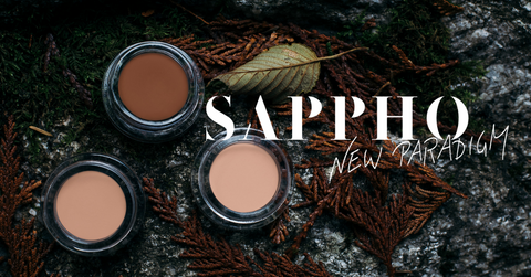 Three open concealer jars on a BC forest bed with the SAPPHO New Paradigm logo in white